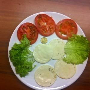 Ciabatta von baguette: 4 dünne Scheiben Mozarella, 2 Blatt Salat und 3 schwindsüchtige Scheibchen Tomaten. Fertig  ist der 2,40 Euro-Imbiss. Großenvergleich mit einer 50-Cent-Münze.